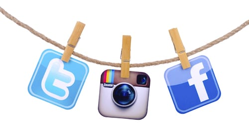 KIEV, UKRAINE - MAY 19, 2015: Popular social media Facebook, Twitter,instagram hanging on the clothesline isolated on white background.
